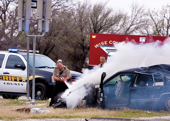 FIERY FINISH - A Wise County sheriff's deputy extinguishes the fire on a car driven by Evan S. Ebel, 28, of Colorado. The engine of the Cadillac burst into flames after Ebel crashed into a rock hauler on U.S. 380 in Decatur at the end of a high-speed pursuit that began in Montague County. Ebel who opened fire on officers after the wreck. Messenger photo by Jimmy Alford
