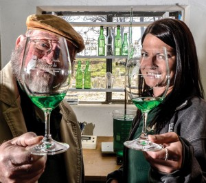 GLASS PRISM - Winemakers Les Constable and Rachel Cook show off a sample of the green wine made with Blanc du Bois grapes. Messenger photo by Joe Duty 
