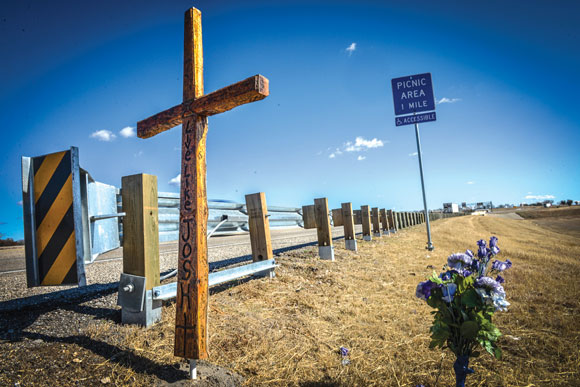 MEMORIAL MARKER - A stained-cedar cross built in memory of Josh Hernandez rises from the side of the road on U.S. 287 in Alvord. The 18-year-old senior from Byron Nelson High School died from injuries sustained in a wreck there last April. The cross was built by Mark Irland. The Sunset resident makes and delivers the crosses at no cost to people who have lost a child or someone else in their life. Messenger photo by Joe Duty