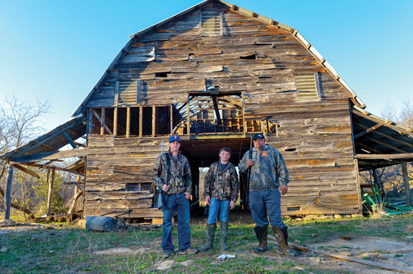 RURAL TRADITION - Andrew Gage, Tyler Chapman and Kory Chapman, all of Decatur, suit up in front of an old farmhouse before going out on a wild hog hunt at night. Messenger photo by Joe Duty 
