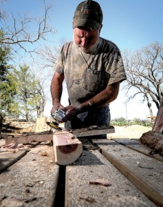 "SCULPTING CROSSES - ""God did the hard work. He grew them. I only shaped them into a cross,"" Mark Irland said as he transforms a cedar tree into a cross. Messenger photo by Joe Duty"