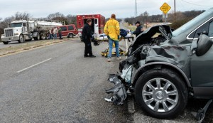 SERIOUS ACCIDENT - Emergency responders wheel Edwina Norris of North Richland Hills to an ambulance Friday morning after a four-vehicle accident at the intersection of Farm Road 920 and Texas 199 south of Boonsville. She was the driver of the Buick Enclave pictured in the foreground. Messenger photo by Joe Duty