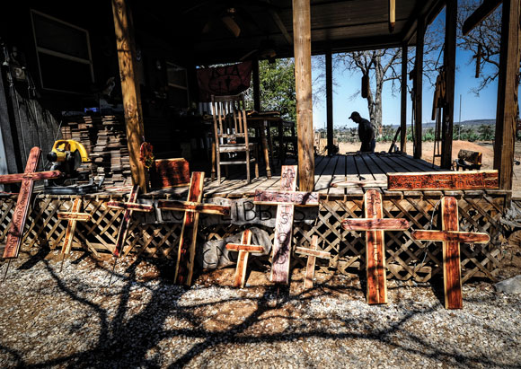 SIGN OF THE CROSS - Mark Irland's cabin in the woods is surrounded by crosses he makes on a daily basis for people dealing with loss. It's his form of therapy after losing a daughter, Meg Irland, in a fatal car wreck near Bridgeport two-and-a-half years ago. Messenger photo by Joe Duty