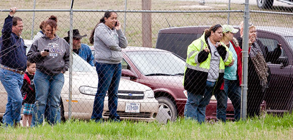WITNESSES - Onlookers stare at the scene of Ebel's fiery crash from the parking lot of a local government building. Messenger photo by Jimmy Alford