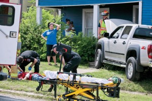 CLOSE CALL - Emergency personnel tend to Coy O'Neal moments after the Decatur resident ran into the porch of a home a block north of the Decatur Square Tuesday. Messenger photo by Jimmy Alford