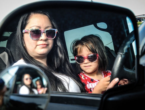 DRIVE TIME - Claudia Bermudez sits in the driver's seat the day after receiving her license. She and her daughter, Valentina, wore sunglasses on the bright, spring morning, which was a bold move for a young woman who previously never drew attention to herself. Messenger photo by Joe Duty