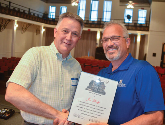 HISTORICAL PHOTOS - Kerry Clower, president of the Wise County Historical Society, presents Messenger photographer Joe Duty with a certificate honoring his work documenting local history on the pages of the newspaper. Duty was honored at a luncheon Monday. Messenger photo by Roy J. Eaton