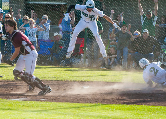JUMPING FOR JOY - Dillon Meadows begins to celebrate as Skylar Black slides in safely with the winning run in the bottom of the seventh. Messenger photo by Jimmy Alford