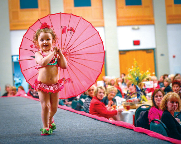 MODELING DEBUT - Chevelle Crisp, 2, of Bridgeport toddles down the runway at Wednesday's Dazzle Me Pink fashion show at the Decatur Civic Center. She's the daughter of Cheyenne and Ethan Crisp. Messenger photo by Joe Duty