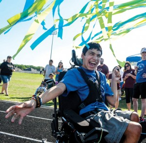 ALL SMILES - J.J. Benavidez of Decatur celebrates a race finish at the Wise County Olympathon Tuesday as peers, teachers and volunteers cheer him on. Special-needs students from across the county were invited to the day-long field day in Bridgeport. Messenger photo by Joe Duty