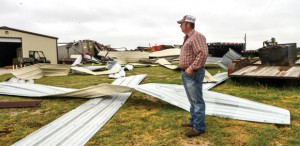 BLOWN OVER - Danny Taylor assesses the damage to his hay barn and vehicles the morning after a possible tornado ripped across his property south of Greenwood. Messenger photo by Joe Duty