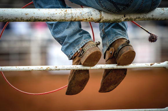 BOOTS DOWN - Boot heels hang on to a bar in the fence surrounding the Bridgeport Riding Club Arena as a cowboy takes a break to watch the action during the first round of this weekend's rodeo. Messenger photo by Joe Duty