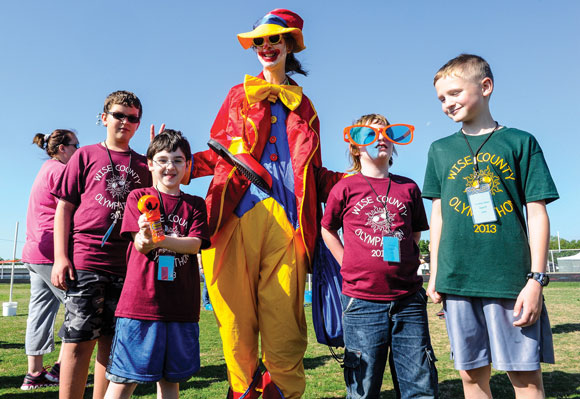 CLOWNING AROUND - Participants of this year's Wise County Olympathon take a break from the field day activities to cut up with Bubbles the Clown, played by Linda Main. Main is a diagnostician for Wise County Shared Services, whose staff organizes the event. Messenger photo by Joe Duty