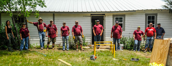COMMUNITY EFFORT - A group of Bridgeport Gives Back volunteers takes a break from ripping up flooring, hanging sheetrock, laying tile and painting cabinets during the complete overhaul of a home - one of several projects taken on during five days of community service May 15-19. Messenger photo by Joe Duty