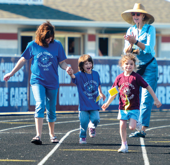 COUNTYWIDE FIELD DAY - Volunteers Kim Myers (left) and Jill Eder encourage Olympathon participants Zulynn Simpson of Decatur and Shanna Perez of Bridgeport with cheers and claps. Special needs students from across the county are invited to the day-long event. Messenger photo by Joe Duty