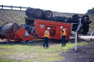 FRAGRANT ROLLOVER - Texas Department of Transportation workers check out the wreckage after a garbage truck flipped over Monday morning at the intersection of Texas 114 and Farm Road 51 South. The wreck injured two people and detoured northbound traffic headed east for hours. Messenger photo by Jimmy Alford