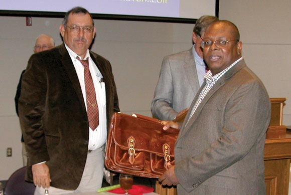 OUTSTANDING JOB - Darnell Willis (right), Natural Resources Conservation Service district conservationist for Wise County, was presented a leather briefcase in recognition of his outstanding work from Alfonso Leal, assistant state conservationist in Weatherford. The award came at the Area V Conservation Awards Banquet Tuesday in Stephenville. Messenger photo by Denny Deady
