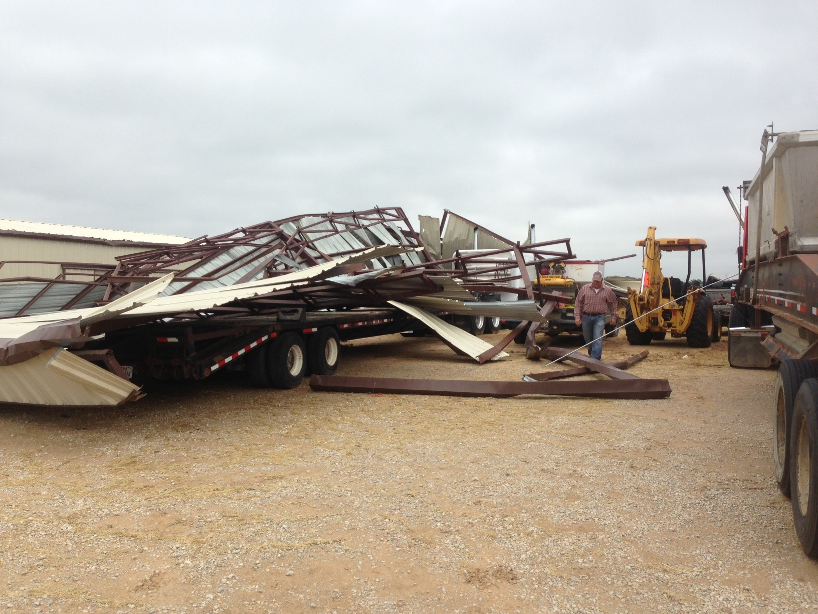 A collapsed barn sits on top of an 18-wheeler flatbed at the home of Danny Taylor near Greenwood. Messenger photo by Joe Duty.