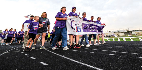 THRIVING AND SURVIVING - Cancer survivors walk the opening lap of the 12th Annual Relay For Life of Wise County Friday. The warriors were honored during a reception before the event's opening ceremony and at a dinner last month. Messenger photo by Joe Duty