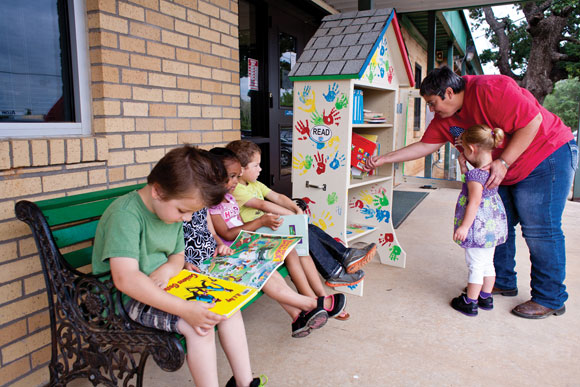 BOOKS FOR ALL - Luisa Horton of Boyd and her granddaughter, Haviana Phillips, peruse the collection of books in the Little Free Library stationed outside Head Start Early Learning Center in Boyd. Alongside them, Haviana's classmates Cooper, Moxy, Jaylen and Caleb become immersed in their picks. Messenger photo by Jimmy Alford