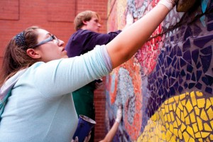 LEAVING A MARK - Marcela Garza and Remi Lane grout the tiled mosaic Friday in Bridgeport. The project was designed and created by the art students. Messenger photo by Jimmy Alford