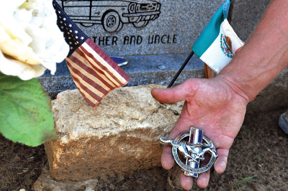 NO MEMENTO - The ornament from a Ford Mustang rests with other items at the grave of Omar Carrillo. Messenger photo by Brandon Evans