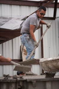 POURING AWAY - Production manager Joel Moraza smooths concrete slated to be the reinforced outer walls of a storm shelter. Felipe Bustos stands on the ground below using a  machine to vibrate and settle the wet concrete into the form. Messenger photo by Jimmy Alford