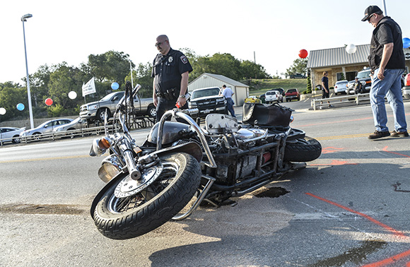 ACCIDENT INVESTIGATION - Bridgeport Officer Nicolas Yates marks the scene of an accident from which the driver of the pictured motorcycle was flown to John Peter Smith Hospital in Fort Worth with serious injuries. The motorcylist was struck by a white pickup truck (pictured directly behind the bike) attempting to pull out from the James Wood Neighborhood Autos car lot.