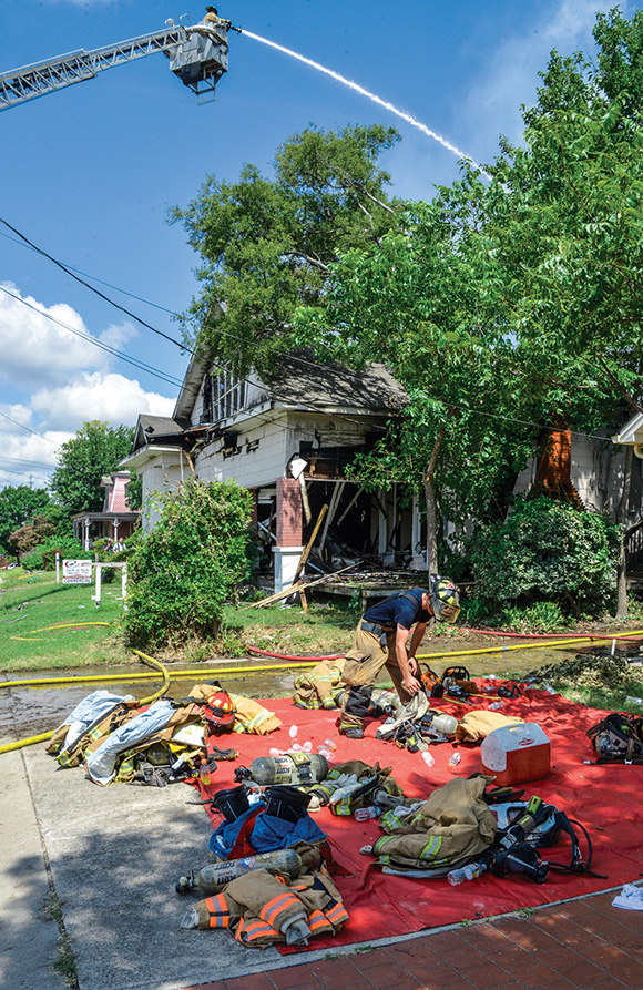 CYCLING IN — After a break, Decatur Firefighter James Carr gears up to fight a multi-family house fire at 500 W. Walnut St. in Decatur Monday. Wise County EMS set up a firefighter rehabilitation center near the scene.