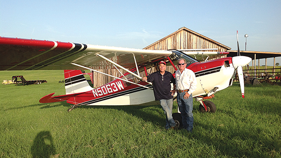 FUELING THE COMPETITION - Pilot Patrick Champagne and Robert Bishop stand with Champagne's plane after he made an emergency landing June 21 in Bishop's pasture near Bowie Municipal Airport.