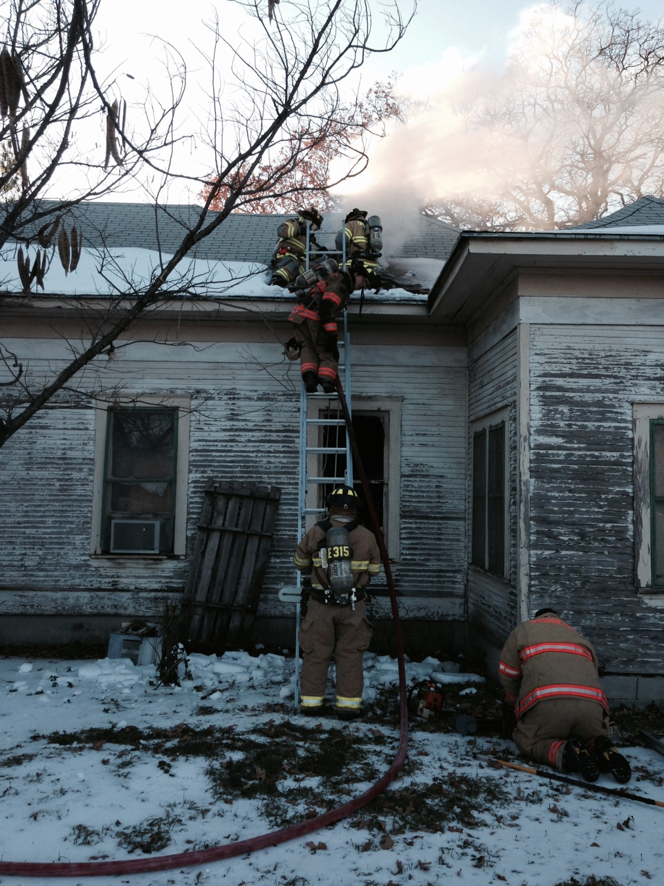 Bridgeport firefighters make access to an attic to attack a house fire Tuesday afternoon west of Bridgeport. Photo by Joe Duty.