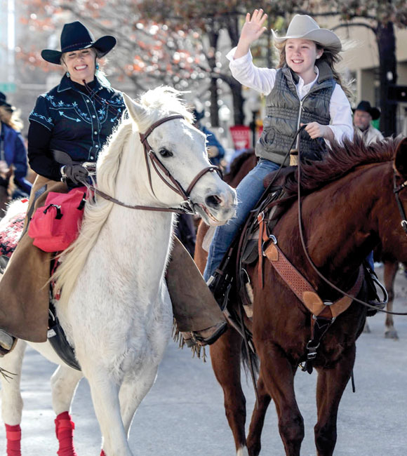 ALL SMILES - Candace Arnette of Decatur and a young rider smile and wave to the crowd during Saturday's stock show parade in Fort Worth. Messenger photo by Joe Duty