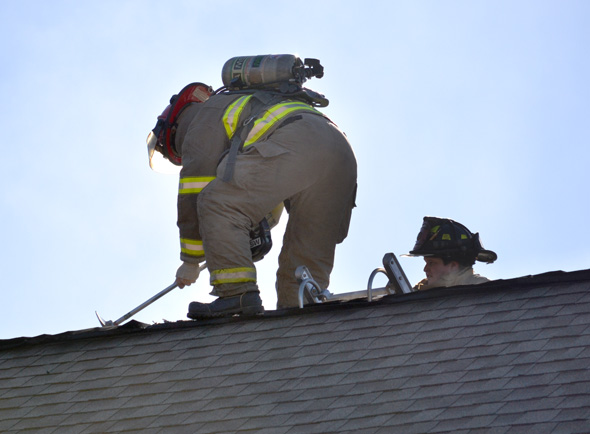 Firefighters break into attic to ensure fire has stopped. Photo by Jimmy Alford.