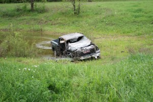 After losing the front right door, the pickup rolled for about 100 more yards until it landed in a stock pond. Messenger photo by Jake Harris.
