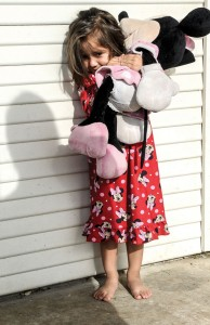 OUT OF THE DARKNESS - Valentina Barrios, 2, stands on the front porch of her Decatur home, clutching a Minnie Mouse doll shortly after waking up one day last week. Valentina's mother, Claudia Bermudez, said much of her own life has been spent living in the shadows as an undocumented immigran. Messenger photo by Joe Duty
