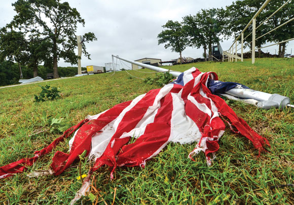 BROKEN MAST - A flag pole in front of the Taylor residence was left bent and broken after a possible tornado ripped through the property and narrowly missed their home Wednesday evening. Messenger photo by Joe Duty